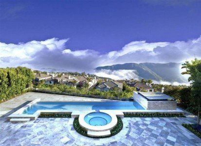 A pool overlooking cloudy mountains in Pacific Palisades.
